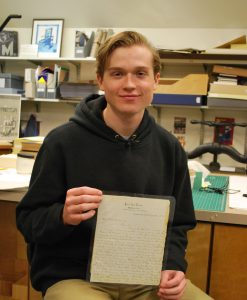 Benjamin Roy posing with handwritten letter