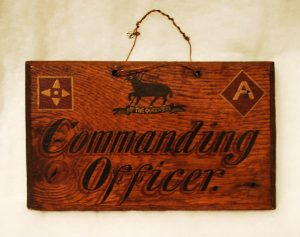 wooden Commanding Officer sign with Royal West Surrey lamb insignia painted at the top.