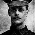 black and white newspaper photograph close up of First World War soldier with a moustache and hat with cap badge of the Queen's Royal West Surrey Regiment