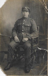 Sepia, full-length photo of seated WWI soldier from the British Army, The Queen's (Royal West Surrey) Regiment