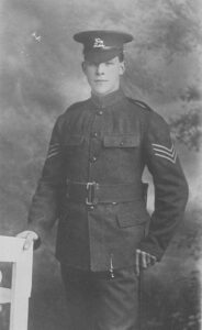 First World War soldier posed, standing for photograph, in uniform with sergeant's stripes visible on his jacket.